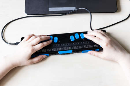 Moscow, Russia - June 5, 2021: hands on keys of Focus 40 Blue Braille Display. Freedom Scientific is the largest manufacturer of assistive technology products for blind and low vision people