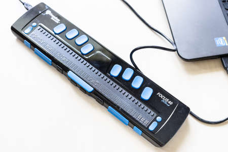 Moscow, Russia - June 5, 2021: Focus 40 Blue Braille Display connected to laptop. Freedom Scientific is the largest manufacturer of assistive technology products for blind and low vision people