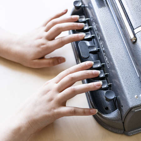 Moscow, Russia - June 5, 2021: fingers on keys of Perkins Brailler braille typewriter. The first Perkins Brailler was produced in 1951 by David Abraham, teacher at the Perkins School for the Blind
