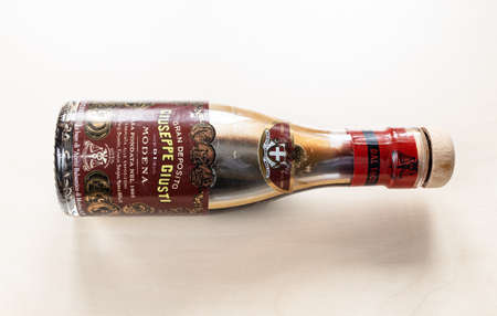 MOSCOW, RUSSIA - JUNE 10, 2021: lying used glass bottle of aged Giuseppe Giusti Aceto Balsamico di Modena on pale board. Giusti family is Italy's oldest Balsamic Vinegar producer since 1605