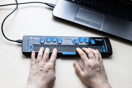 Moscow, Russia - June 5, 2021: reading with Focus 40 Blue Braille Display. Freedom Scientific is the largest manufacturer of assistive technology products for blind and low vision people