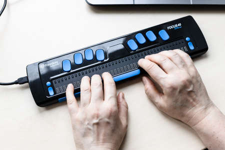 Moscow, Russia - June 5, 2021: female hands on Focus 40 Blue Braille Display. Freedom Scientific is the largest manufacturer of assistive technology products for blind and low vision people