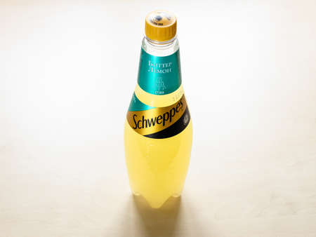 MOSCOW, RUSSIA - JUNE 10, 2021: russian edition plastic bottle of Schweppes Bitter Lemon water on light brown board. Schweppes introduced its brand of bitter lemon in 1957
