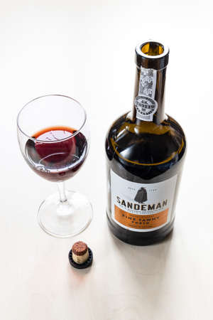 MOSCOW, RUSSIA - JUNE 10, 2021: wine glass, cork and open bottle of Sandeman fine tawny porto wine. Sandeman is brand of Port and Sherry wines founded in 1790 in Portugal