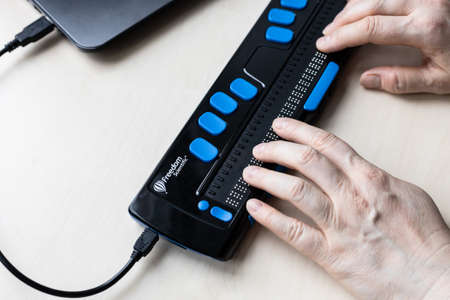 Moscow, Russia - June 5, 2021: fingers read with Focus 40 Blue Braille Display. Freedom Scientific is the largest manufacturer of assistive technology products for blind and low vision people