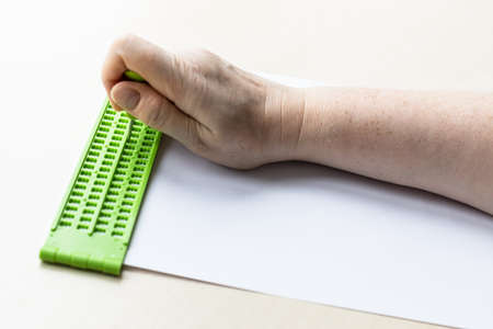 female hand writes words in braille with slate and stylus close up