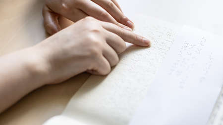 reading book and note with braille text close up
