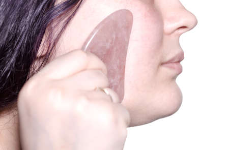 massaging female face with quartz scraper close up in technique of traditional chinese gua sha massage isolated on white background