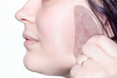 woman massages cheek with quartz scraper close up in technique of traditional chinese gua sha massage