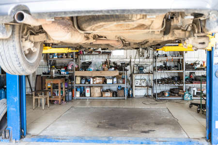 bottom view of lifted old car in car workshop (focus on the muffler in center of car's bottom) 版權商用圖片