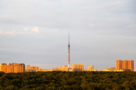 city park and high-rise houses on horizon illuminated by sunset sun Banque d'images