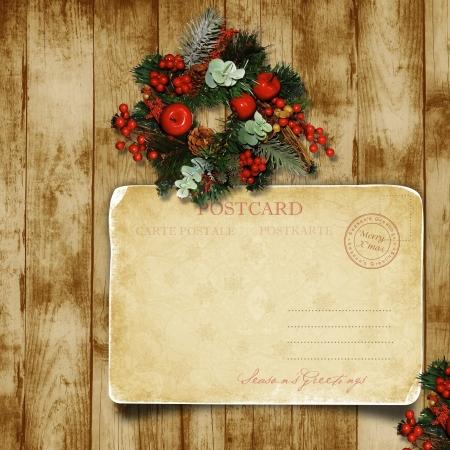 Christmas wreath on the wood door with a Christmas postcard