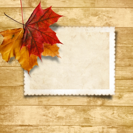 Wooden background with autumn leaves and old card  Wooden background with autumn leaves and old card  photo
