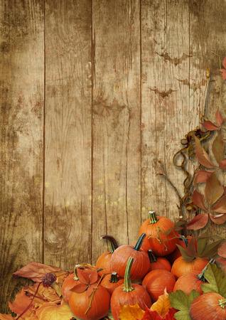 cuerno de la abundancia: Hojas de otoño y calabazas sobre un fondo de madera Hojas de otoño y calabazas sobre un fondo de madera Foto de archivo