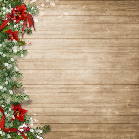 Christmas wood background with poinsettia and firtree Standard-Bild