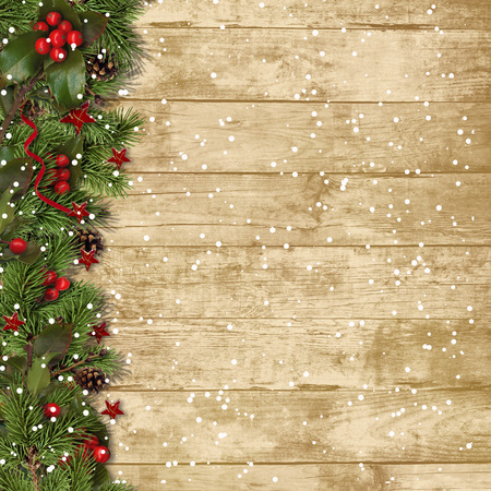 Christmas fir branches and holly on wood background Standard-Bild