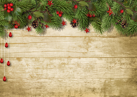 Christmas fir branches and holly on wood background Фото со стока