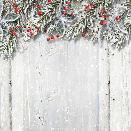 クリスマスのモミの枝とホリーと木製の背景 写真素材