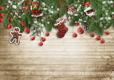 christmas wallpaper: Christmas fir tree with cookie, holly and decoration on wood Stock Photo