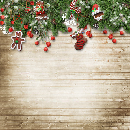 WOOD BACKGROUND: Christmas fir tree with cookie, holly and decoration on wood Stock Photo
