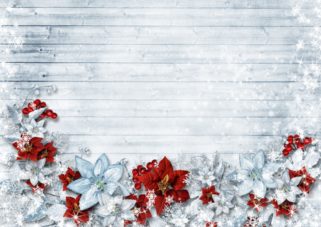 Christmas border with poinsettia and winter flowers on wood