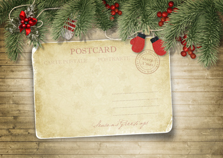 Holidays vintage background with red mittens, holly and postcard