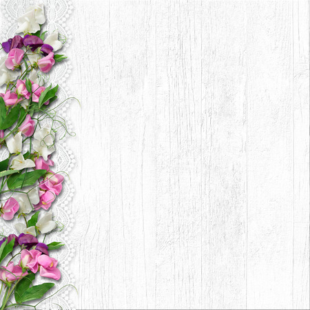 Border of beautiful spring flowers on a white wooden background Фото со стока