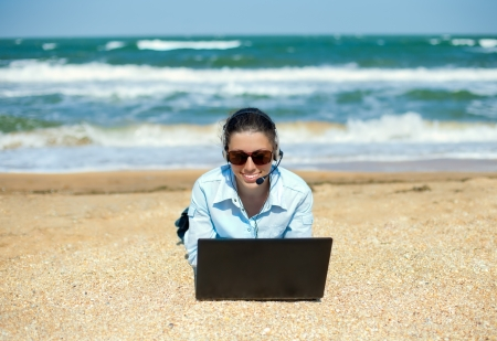 Business woman talking using her laptop on the beach