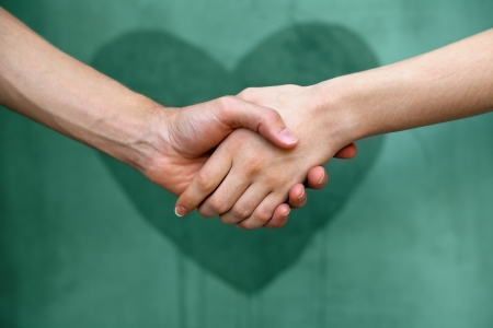 Man and woman shaking hands with a heart painted wall in background Stock Photo
