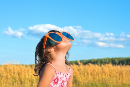 Happy little girl with big sunglasses looking at the sky photo