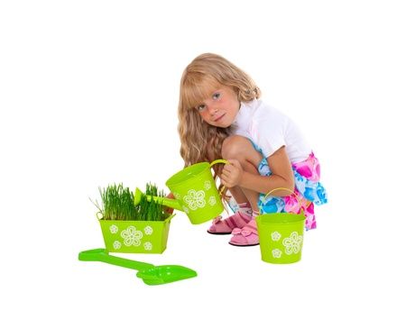 Little smiling girl watering grass isolated on white background
