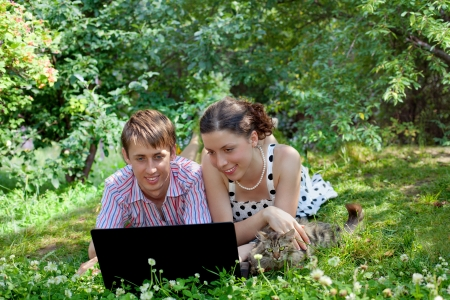 Young woman, man and cat lying with laptop on the grass in the garden photo
