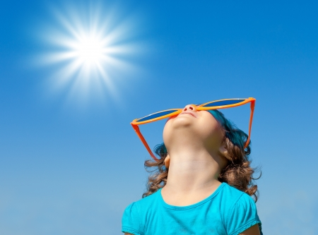 big smile: Happy little girl with big sunglasses looking at the sky Stock Photo