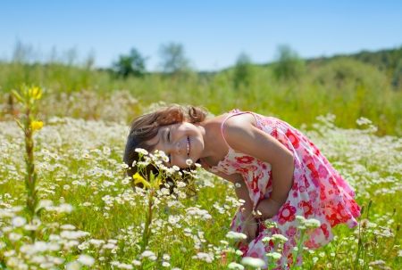 Happy little girl playing at the flower field
