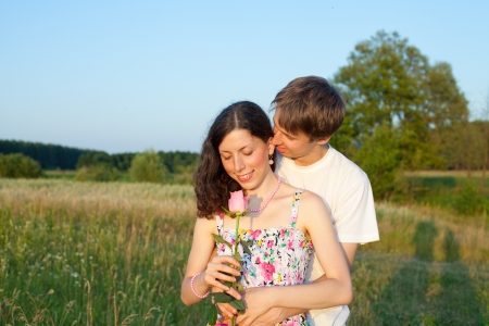 Loving young man hugging his girlfriend with rose in their hands