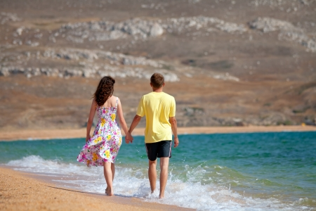 Young couple holding hands and walking carefree on the beach on summer vacation photo
