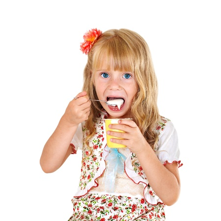 Little girl eating yogurt isolated on white background photo