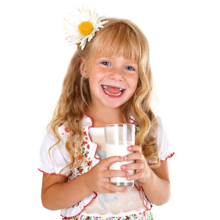 Little smiling girl holding a glass of milk isolated on white background