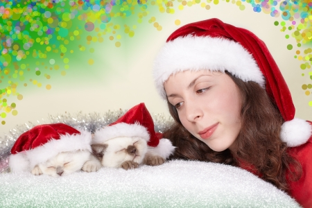 Smiling girl admires sleeping cats wearing Santa s hat photo