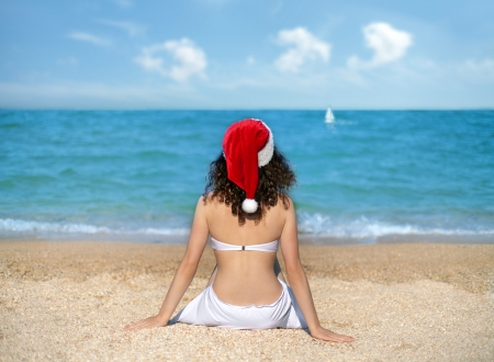 Young girl wearing Santa s hat sitting on the beach photo