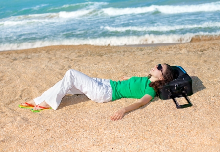 Young happy girl with traveling bag relaxing on the beach photo