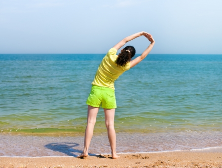 Yong woman doing morning exersise on the beach photo