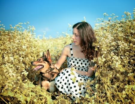Young happy girl with dog on the buckwheat field photo