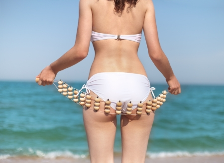 Young slim woman doing self anti cellulite massage on the beach Stock Photo - 18000117