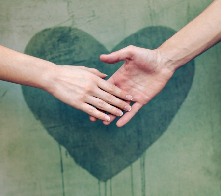 hands holding heart: Man touching woman s hand with a heart painted wall in background Stock Photo