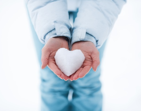Heart made of snow in female hands
