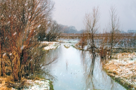 Winter river in snowy weather photo
