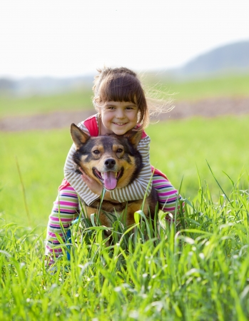 Happy little girl playing with dog on the grass