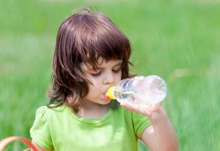 Little girl drinking water from bottle