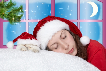 Young girl and little cat wearing Santa s hat sleeping photo